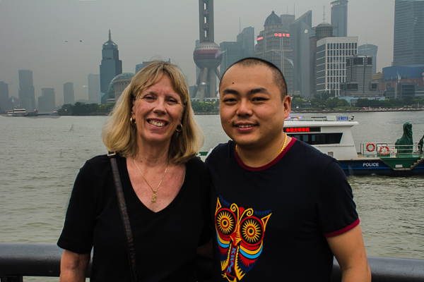 Rebecca and tour director Addison with the Huangpu River in the background in Shanghai.